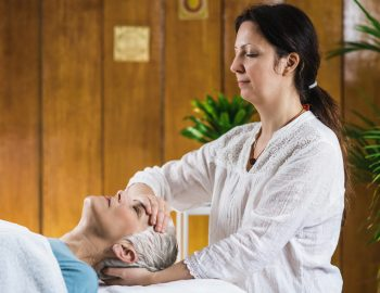 Marma therapy.  Beautiful senior woman lying on massage table and enjoying Ayurveda facial treatment. Marma therapy practitioner treating Madhya Chibuk neck prana point. Facial acupressure points. Acupressure point for skin improvement.